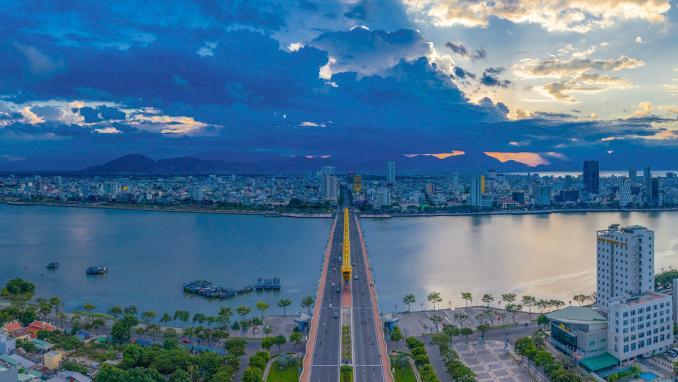 """Cầu Rồng thưa thớt xe lúc gần 18h ngày 10/8. Cầu Rồng - có kiến trúc độc đáo mô phỏng hình con rồng thời Lý, bắc qua sông Hàn, nối sân bay quốc tế với các bãi biển tuyệt đẹp và cũng là cây cầu biểu tượng của du lịch Đà Nẵng. Đà Nẵng có những tên gọi như """"thành phố của những cây cầu"""" hay """"thành phố ánh sáng"""" với nhiều cao ốc và các khu nghỉ dưỡng, được công nhận là đô thị loại I vào năm 2003, là trung tâm của vùng duyên hải Nam Trung Bộ. Ảnh: Vnexpress."""